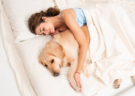 Female woman sleep on white bed at home with her lovely labrador retriever dog. Pet therapy hugging indoor activity. Stay home