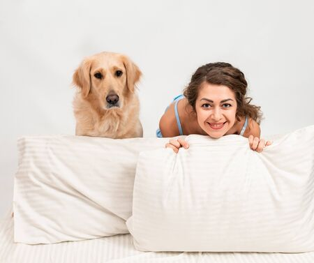 Cheerful Female woman sleep in pajamas lying in bed with her golden retriever dog. Romantic relationship human and dog concept