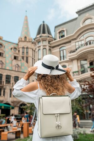Stylish female girl in white dress discovering and searching famous places, traveling alone in Europe. Fashion of young girl brunette woman walking on old streets. Lifestyle, travel, vacation, tourism. Back view