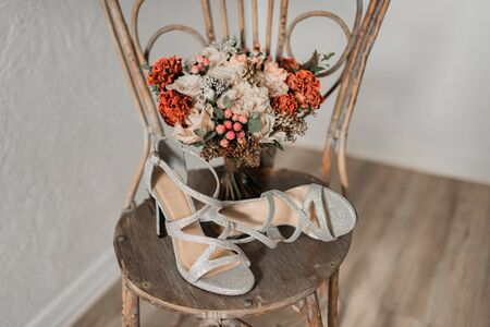 Bridal morning details. Wedding bouquet of red, beige flowers and silver shoes.