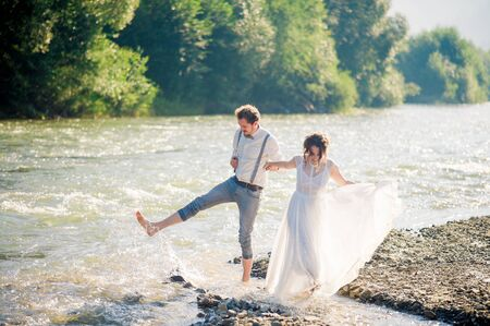 happy, emotional gorgeous bride and stylish groom having fun, splashed with water. Wedding couple running along the mountain river with feet.