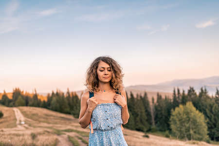 Young pretty curly woman sitting and enjoying on the mountains top. Beautiful young cheerful female model. Young woman outdoors. Mountains land