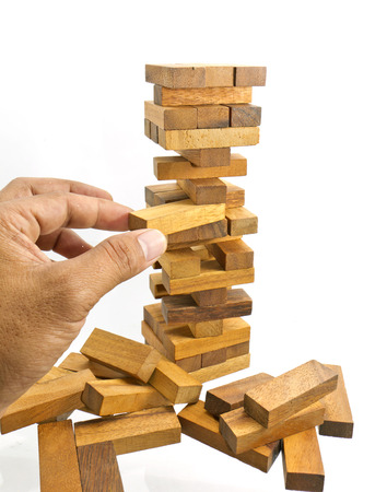 The hand establishes a wooden cube. It is isolated on a white  Stock Photo