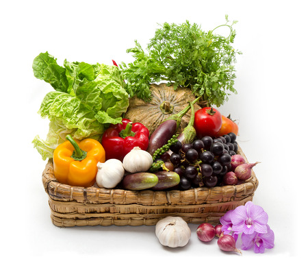 Variety of raw vegetables in wicker basket isolated on white photo