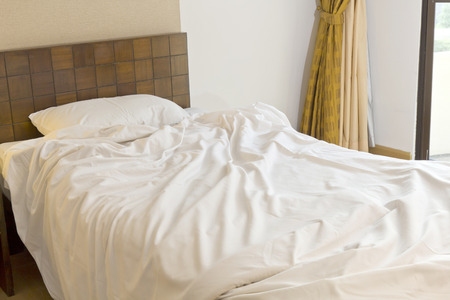 Unmade bed with white bedding