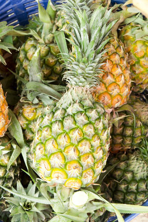 One over another a lot of pineapples on the market