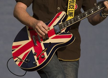 played: British flag colored guitar being played live on stage