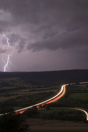 streak lightning: German Autobahn (motorway) at night with lightning in the back