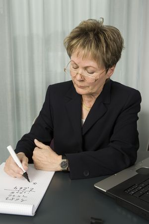 Senior business woman with laptop and pen calculating financial data. Stock Photo - 2807655