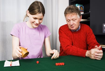 Teenage girl and her grandfather playing dice photo