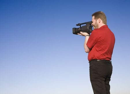 Videographer shooting handheld footage with prosumer camcorder, shot against blue sky. Stock Photo - 2807645