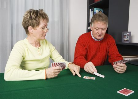 Senior couple playing cards at home photo