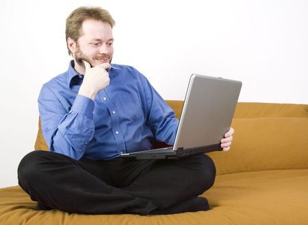 Casual businessman with laptop working on a couch. Stock Photo - 2902166