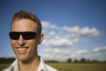 Cool young man with sunglasses smiling. Sunny summer setting with few clouds. Extremely narrow depth of field. Stock Photo - 2946245