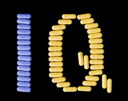 iq: Colourful pills spelling the acronym IQ isolated on black.