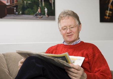 Senior casual man reading the newspaper in his living room. photo