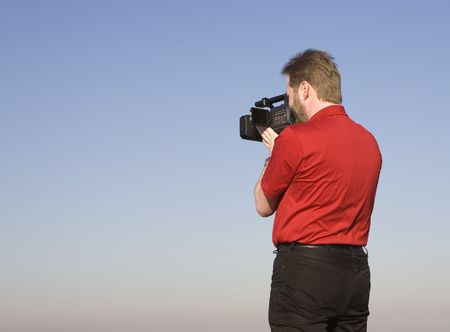 Videographer shooting handheld footage with prosumer camcorder photo
