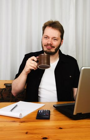 Middle aged man working at home with laptop enjoying his morning coffee. photo