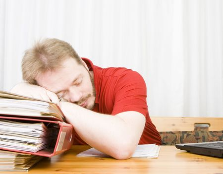 Casual businessman falling asleep over his tax work at the kitchen table. photo
