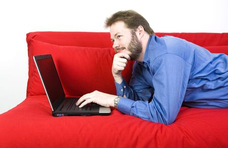 Casual businessman with laptop working on a couch. photo