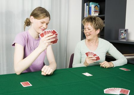 Teenage girl and her grandmother playing cards. photo