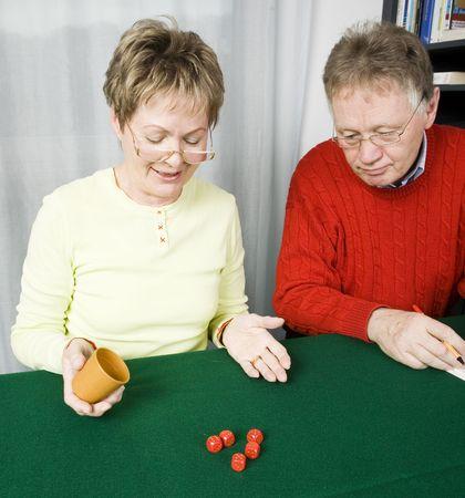 Senior couple playing dice - woman rolls full house photo