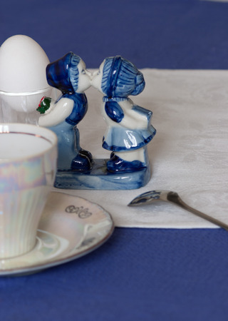 romantic background: Kissing boy and girl. blue and white statue stands next to a pair of tea, boiled egg and spoon on a blue tablecloth and white napkin