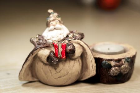 suspenso: figura de Santa Claus con regalo de color rojo en las manos, y un candelabro con un único regalo candle.Focus.