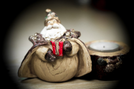 suspenso: figure of Santa Claus with red gift in the hands, and a candlestick with a candle.Focus only gift.