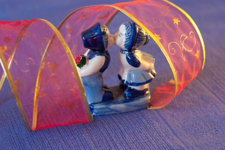 desayuno romantico: Kissing boy and girl. blue and white statue stands next to a pair of tea on a blue tablecloth Foto de archivo