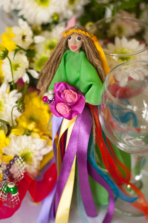 ukrainian ethnicity: Decor for the tabletop flower arrangement. Doll in a green dress with multi-colored ribbons and bouquet in her hands and wearing a crown of yellow ribbons