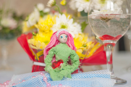 tabletop: Decor for the tabletop flower arrangement. Doll with pink hair in the form of the goddess of spring. In the background, a lot of flowers Stock Photo