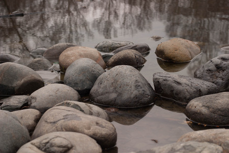 large rocks: round large rocks laid along the pond in the park Stock Photo