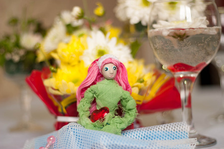 flower arrangement: Decor for the tabletop flower arrangement. Doll with pink hair in the form of the goddess of spring. In the background, a lot of flowers Stock Photo