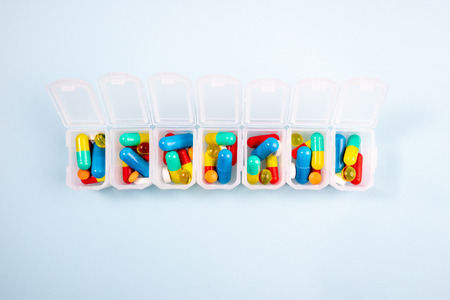 Weekly organizer with pills on blue background. Pharmaceutical medicine tablets, capsules and pills in box