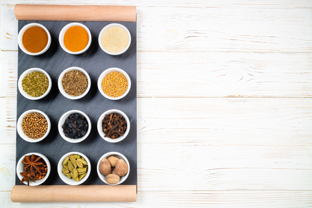 Various spices in bowls on a black slate board. Spices background. Top view, copyspace 写真素材