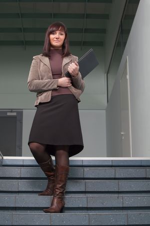 school girl sexy: business woman standing on staisr with the folder in her arms Stock Photo