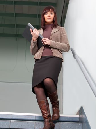 business woman standing on staisr with the folder in her arms Stock Photo - 6433153