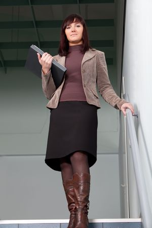 business woman standing on staisr with the folder in her arms photo