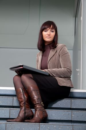 business woman sitting on staisr with the folder in her arms photo
