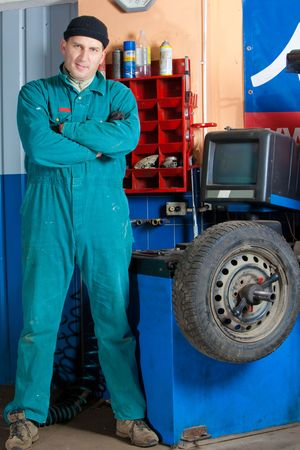 mechanic changing car tire in garage Stock Photo - 6469023