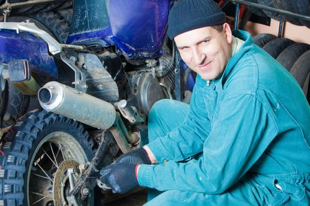mechanic changing car tire in garage Stock Photo