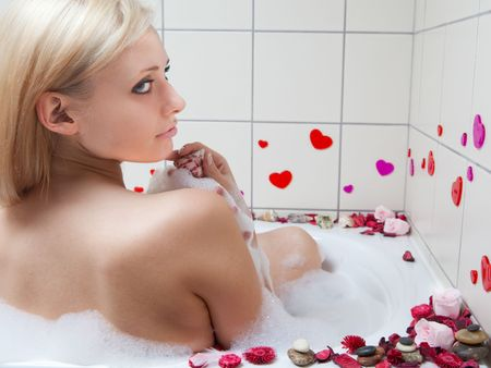 young adult blond woman having spa in bath photo