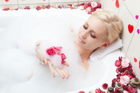bathing beauty: young adult blond woman having spa in bath