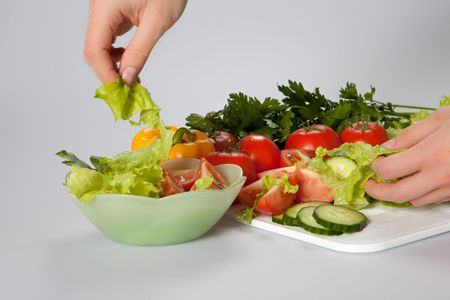 woman adding lettuce to the salad photo