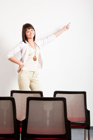woman making a presentation in class, pointing right with finger at board