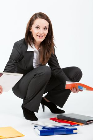 business woman collecting folders with documents from floor photo