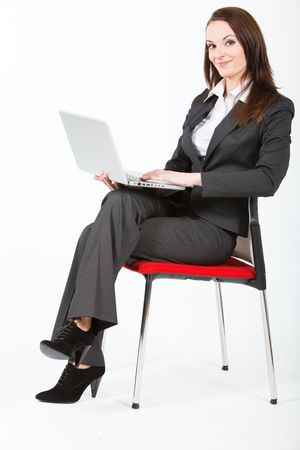business woman sitting and working with laptop on her knees photo