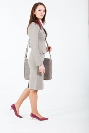 business woman walking with computer case on her shoulder photo
