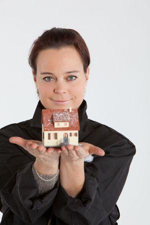 junge Erwachsene Frau kleines Haus in Ihren Händen halten